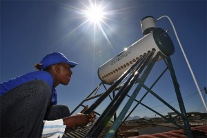 Person on roof working on a solar water heater in Africa